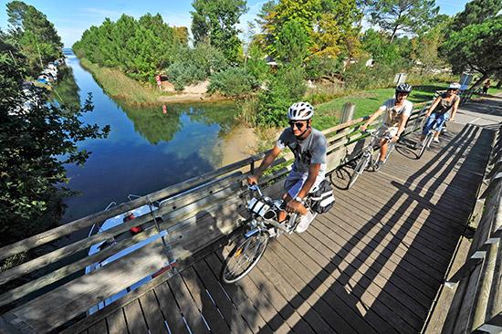 Radfahrer fahren über eine kleine Holzbrücke in Les Landes.