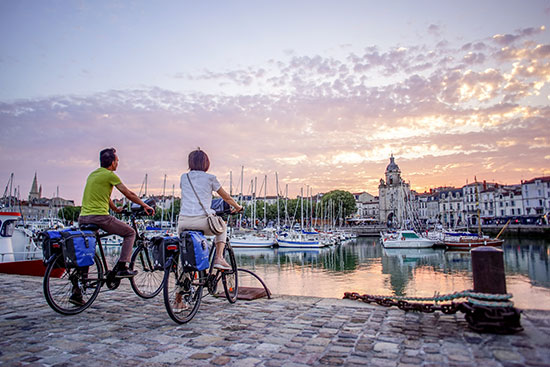 Zwei Radfahrer genießen den Sonnenuntergang in La Rochelle