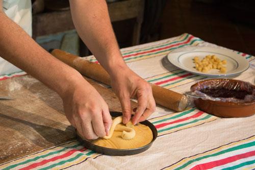 Der Konditor vom Musée du gâteau basque verziert den Kuchen mit dem traditionellen baskischen Kreuz (Lauburu)