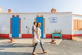 Ein Paar schlendert vorbei an einem Fischerhaus im marrokanischen Viertel von Saint-Gilles-Croix-de-Vie.