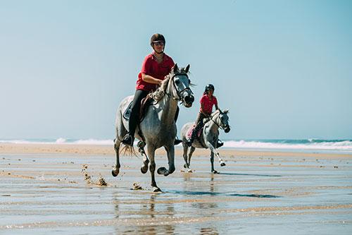 Reiter galoppieren am Strand in Les Landes an der französischen Atlantikküste